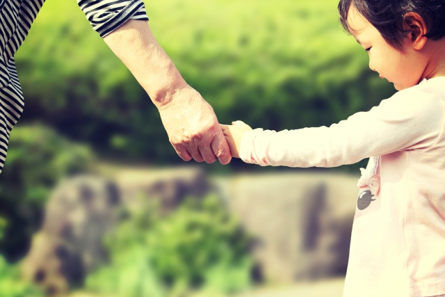 おばあちゃんと手を繋ぐ子供